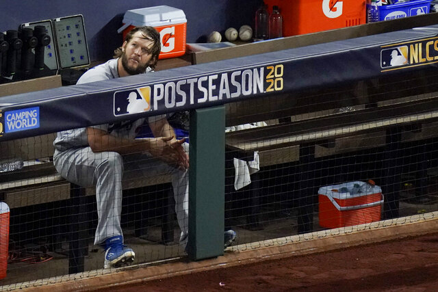 Los Angeles Dodgers starting pitcher Clayton Kershaw sits in the dugout after leaving the game during the sixth inning in Game 4 of a baseball National League Championship Series against the Atlanta Braves Thursday, Oct. 15, 2020, in Arlington, Texas. (AP Photo/Sue Ogrocki)