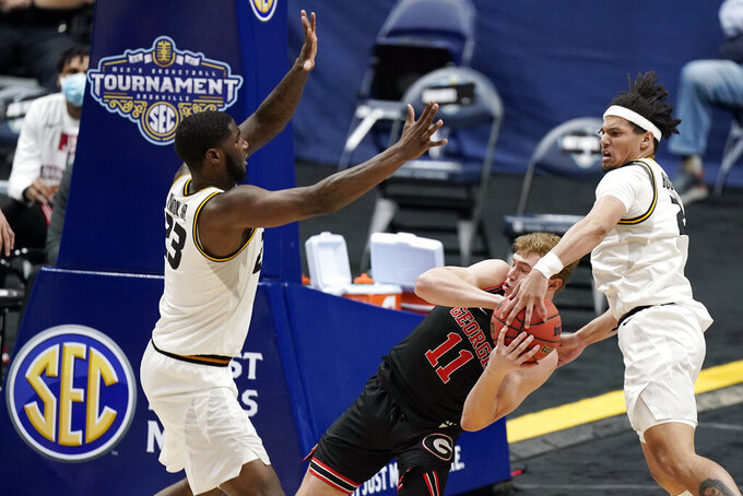 Georgia's Jaxon Etter (11) is trapped between Missouri's Jeremiah Tilmon (23) and Drew Buggs, right, in the second half of an NCAA college basketball game in the Southeastern Conference Tournament Thursday, March 11, 2021, in Nashville, Tenn. (AP Photo/Mark Humphrey)