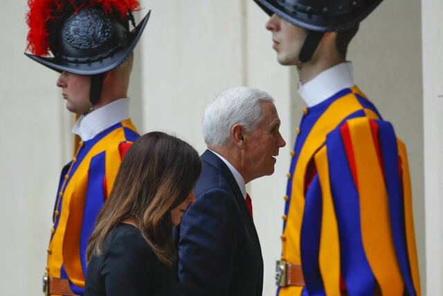 US Vice President Mike Pence and his wife Karen walk past Vatican Swiss Guards as they arrive at the San Damaso courtyard at the Vatican ahead of their private audience with Pope Francis, Friday, Jan. 24, 2020. (AP Photo/Domenico Stinellis)