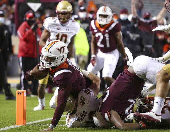 Virginia Tech quarterback Hendon Hooker, left, scores in the first half of an NCAA college football game against Boston College in Blacksburg Va. Saturday, Oct. 17, 2020. (Matt Gentry/The Roanoke Times via AP, Pool)
