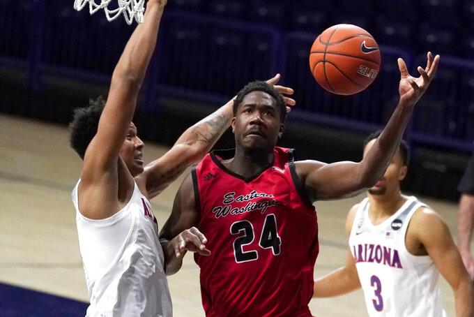 Eastern Washington guard Kim Aiken Jr. (24) drives past Arizona forward Ira Lee (11) during the second half of an NCAA college basketball game, Saturday, Dec. 5, 2020, in Tucson, Ariz. Arizona won 70-67. (AP Photo/Rick Scuteri)