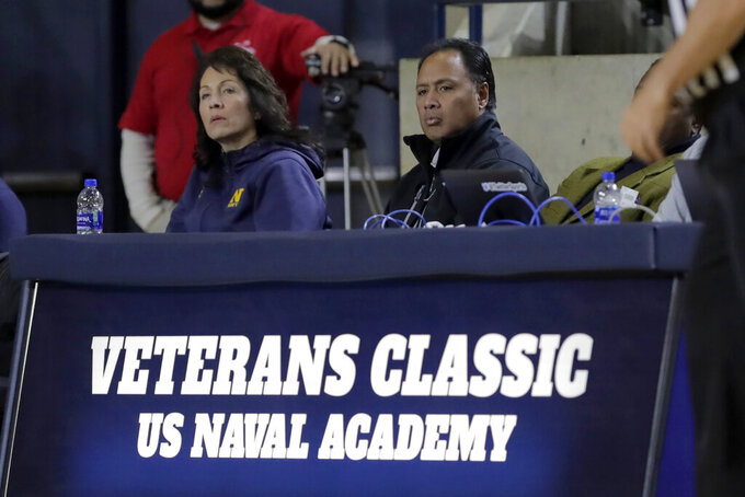 Navy football head coach Ken Niumatalolo, right, sits with his wife, Barbara Niumatalolo, while watching the first half of an NCAA college basketball game against East Carolina at the Veterans Classic Tournament, Friday, Nov. 8, 2019, in Annapolis, Md. (AP Photo/Julio Cortez)