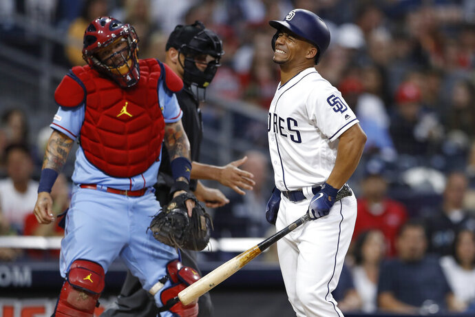 San Diego Padres' Francisco Mejia, right, reacts after getting hit by a pitch as St. Louis Cardinals catcher Yadier Molina, left, watches during the second inning of a baseball game Saturday, June 29, 2019, in San Diego. (AP Photo/Gregory Bull)