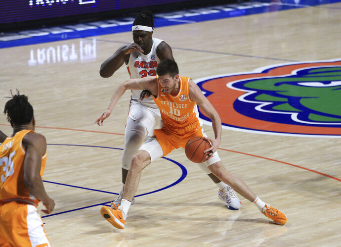 Tennessee forward John Fulkerson (10) dribbles past Florida center Jason Jitoboh (33) during the first half of an NCAA college basketball game Tuesday, Jan. 19. 2021, in Gainesville, Fla. (AP Photo/Matt Stamey)