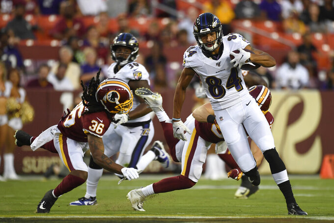 Baltimore Ravens wide receiver Antoine Wesley (84) carries the ball past Washington Redskins defensive back Adonis Alexander (36) during the first half of an NFL preseason football game at FedEx Field in Landover, Md., Thursday, Aug. 29, 2019. (AP Photo/Susan Walsh)