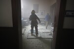 A firefighter walks inside the Congress building after protesters set a part of the building on fire, in Guatemala City, Saturday, Nov. 21, 2020. Hundreds of protesters were protesting in various parts of the country Saturday against Guatemalan President Alejandro Giammattei and members of Congress for the approval of the 2021 budget that reduced funds for education, health and the fight for human rights. (AP Photo/Moises Castillo)