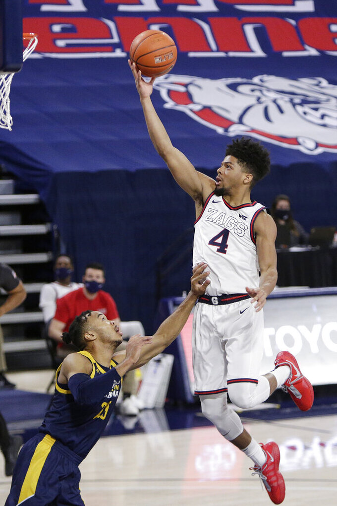 Gonzaga guard Aaron Cook (4) shoots over Northern Arizona guard Cameron Shelton (20) during the second half of an NCAA college basketball game in Spokane, Wash., Monday, Dec. 28, 2020. Gonzaga won 88-58. (AP Photo/Young Kwak)
