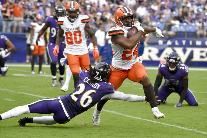 Cleveland Browns running back Nick Chubb (24) avoids a tackle from Baltimore Ravens cornerback Maurice Canady (26) before scoring a touchdown run during the second half of an NFL football game Sunday, Sept. 29, 2019, in Baltimore. (AP Photo/Brien Aho)