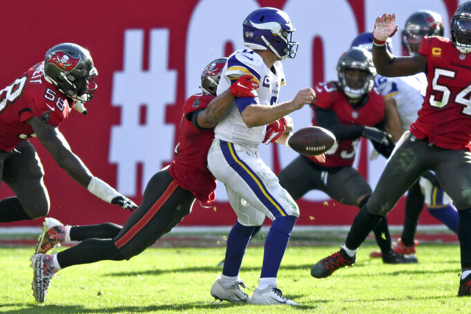Minnesota Vikings quarterback Kirk Cousins (8) loses the football after a hit by Tampa Bay Buccaneers strong safety Antoine Winfield Jr. (31) during the second half of an NFL football game Sunday, Dec. 13, 2020, in Tampa, Fla. Cousins recovered the football. (AP Photo/Jason Behnken)