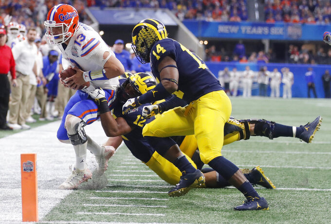 Michigan linebacker Josh Ross (12) tackles Florida quarterback Feleipe Franks (13) during the first half of the Peach Bowl NCAA college football game, Saturday, Dec. 29, 2018, in Atlanta. (AP Photo/John Bazemore)
