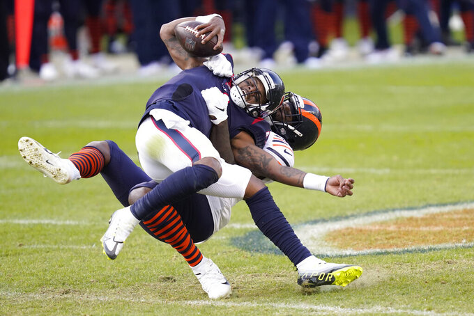 Houston Texans quarterback Deshaun Watson (4) is sacked by Chicago Bears' Mario Edwards (97) during the second half of an NFL football game, Sunday, Dec. 13, 2020, in Chicago. (AP Photo/Charles Rex Arbogast)