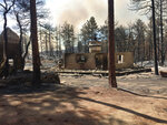 This photo provided by Rusty Bowers shows the remains of Arizona House Speaker Rusty Bowers' family weekend home near several miles southeast of Miami, Ariz., Tuesday, June 8, 2021, that was destroyed by a wildfire the day before. Bowers used the home in the remote mountains as a family retreat and often did his artwork there. (Elijah Cardon/Rusty Bowers via AP)