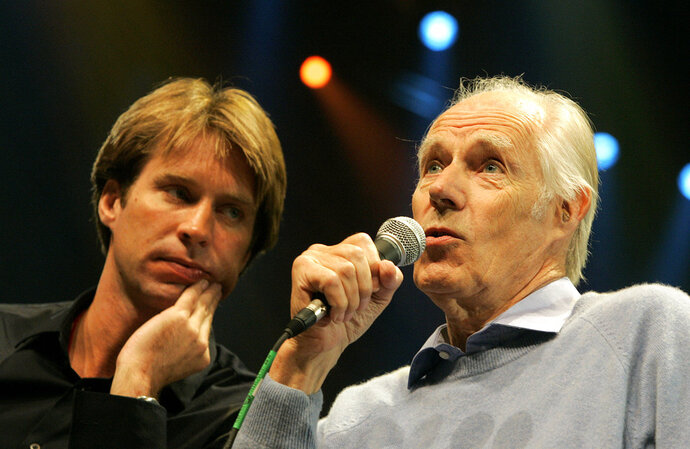FILE - In this May 24, 2006 file photo, Giles Martin, left, listens as his father, original Beatles producer George Martin speaks after a sneak preview of a new Beatles-themed Cirque du Soleil show,