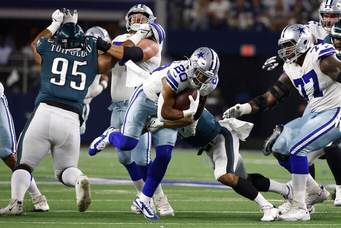 Dallas Cowboys running back Tony Pollard (20) runs the ball between Philadelphia Eagles defensive tackle Marlon Tuipulotu (95) and offensive tackle Tyron Smith (77) in the first half of an NFL football game in Arlington, Texas, Monday, Sept. 27, 2021. (AP Photo/Ron Jenkins)