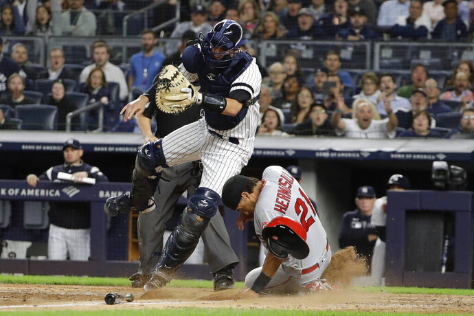 Los Angeles Angels' Michael Hermosillo (21) slides past New York Yankees catcher Kyle Higashioka to score on a throwing error by relief pitcher Adam Ottavino during the sixth inning of a baseball game Wednesday, Sept. 18, 2019, in New York. (AP Photo/Frank Franklin II)