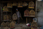 An Afghan bird seller holds a cage at a bird market in Kabul's Old City, Afghanistan, Tuesday, Sept. 14, 2021. It is feared Afghanistan could further plunge toward famine and economic collapse after the chaos of the past month, which saw the Taliban oust the government in a lightning sweep as U.S. and NATO forces exited the 20-year war. (AP Photo/Bernat Armangue)