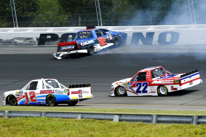 Stewart Friesen (52) crashes into the wall on the opening lap of a NASCAR Truck Series auto race as Gus Dean (12) and Austin Wayne Self (22) drive past, Saturday, July 27, 2019, in Long Pond, Pa. (AP Photo/Derik Hamilton)