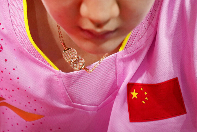 China's Chen Meng wears necklace featuring rackets during the table tennis women's singles gold medal match at the 2020 Summer Olympics, Thursday, July 29, 2021, in Tokyo. (AP Photo/Kin Cheung)