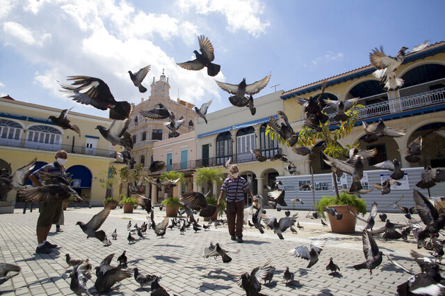 Pigeons take flight in an empty Plaza Vieja in Havana, Cuba, Tuesday, June 23, 2020. Nearly three months of a near-total shutdown of commerce, transportation, and public spaces, combined with health monitoring and virus testing has led to the virtual elimination of COVID-19 in Cuba. (AP Photo/Ismael Francisco)