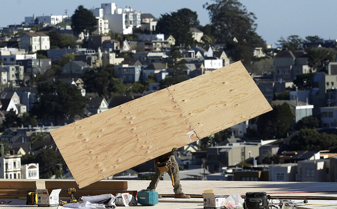 In this March 28, 2018 photo, a construction crew works on a roof in San Francisco.California's unemployment rate edged up slightly in March even as the state continued adding jobs. The state Employment Development Department reported Friday, April 19, 2019 that the rate increased a tenth of a percentage point over February, to 4.3 percent.   (AP Photo/Jeff Chiu)