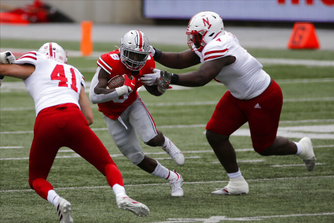 Ohio State running back Trey Sermon, center, tries to run upfield between Nebraska defenders Garrett Snodgrass, left, and Keem Green during the second half of an NCAA college football game Saturday, Oct. 24, 2020, in Columbus, Ohio. (AP Photo/Jay LaPrete)