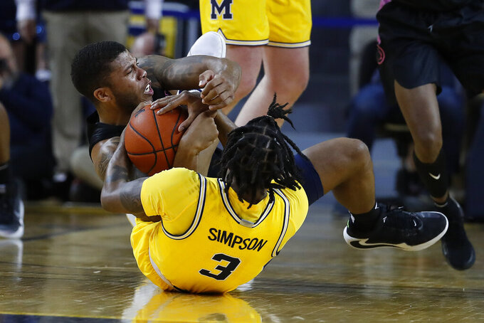 Michigan guard Zavier Simpson (3) and Penn State guard Myles Dread (2) battle for a loose ball in the first half of an NCAA college basketball game in Ann Arbor, Mich., Wednesday, Jan. 22, 2020. (AP Photo/Paul Sancya)