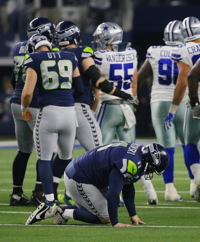Seattle Seahawks place kicker Sebastian Janikowski (11) falls to the ground after suffering an unknown injury to his left leg attempting a long field goal attempt against the Dallas Cowboys in the first half of the NFC wild-card NFL football game in Arlington, Texas, Saturday, Jan. 5, 2019. (AP Photo/Roger Steinman)