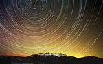 FILE  - In this undated file photo made with a slow shutter speed, stars leaves trails of light over Mount Katahdin near Millinocket, Maine. The director of the Baxter State Park, Eben Sypitkowski, is floating the idea dropping the