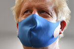 Britain's Prime Minister Boris Johnson, wearing a face mask, visits the headquarters of the London Ambulance Service NHS Trust in London, Monday July 13, 2020. (Ben Stansall/Pool via AP)
