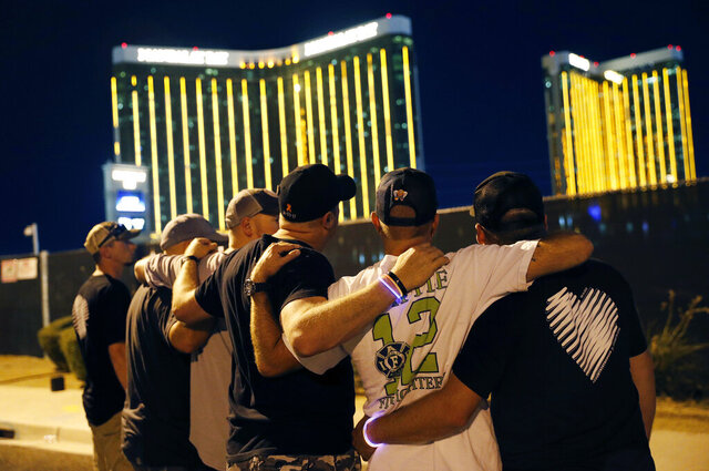 File - In this Oct. 1, 2018, file photo, survivors return to the scene of a mass shooting on the first anniversary  in Las Vegas. Nevada's U.S. senators say federal officials have released some of a $16.7 million grant to help survivors of the October 2017 mass shooting on the Las Vegas Strip. Sens. Catherine Cortez Masto and Jacky Rosen issued a statement saying funds were released after they wrote to U.S. Attorney General William Barr on Jan. 15, 2020, saying money for July through December 2019 had not been disbursed by the Department of Justice. (AP Photo/John Locher, File)