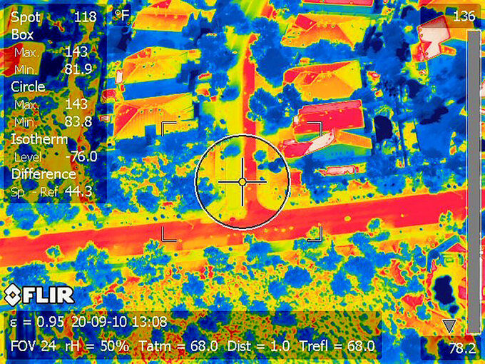 "This Arizona State University thermal image photo shows a Phoenix street coated half with new, lighter-colored pavement to the left of the crosshairs, showing as much cooler in yellow than the original blacktop at right in red, on Sept. 10, 2020. A team from Arizona State University is working with the city of Phoenix on a pilot program studying the use of ""cool pavement"" to reduce the heat island effect, a phenomenon that raises temperatures in urban areas covered by asphalt and concrete. (Arizona State University via AP)"