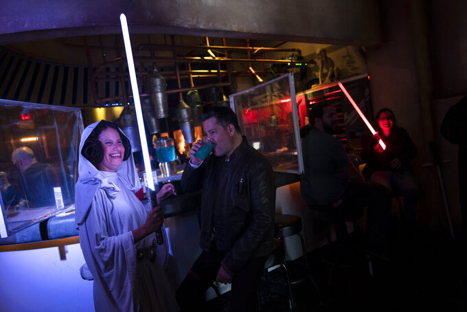 Elen Monocroussos, left, and boyfriend, James Stevens, are dressed in Star Wars costumes as they celebrate the Star Wars Day at Scum and Villainy Cantina, a geekbar located on Hollywood Blvd, in Los Angeles, Tuesday, May 4, 2021. California has the lowest infection rate in the country. Los Angeles County, which is home to a quarter of the state's nearly 40 million people and has endured a disproportionate number of the state's 60,000 deaths, didn't record a single COVID-19 death Sunday or Monday, which was likely due to incomplete weekend reporting but still noteworthy. (AP Photo/Jae C. Hong)