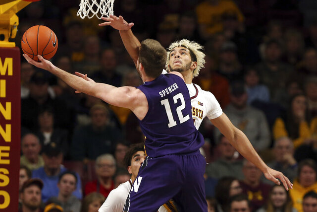 Northwestern's Pat Spencer tries to shoot the ball against Minnesota's Jarvis Omersa during an NCAA college basketball game Sunday, Jan. 5, 2020, in Minneapolis. (AP Photo/Stacy Bengs)