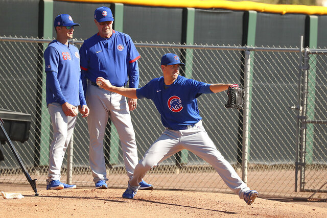 Kyle Hendricks pitches a bullpen while pitching coach Tommy Hottovy (left) and Rick Sutcliffe (right) observe at Cubs Spring Training facility, Mesa, Ariz.,. Thursday, Feb. 13, 2020.  (John Antonoff/Chicago Sun-Times via AP)