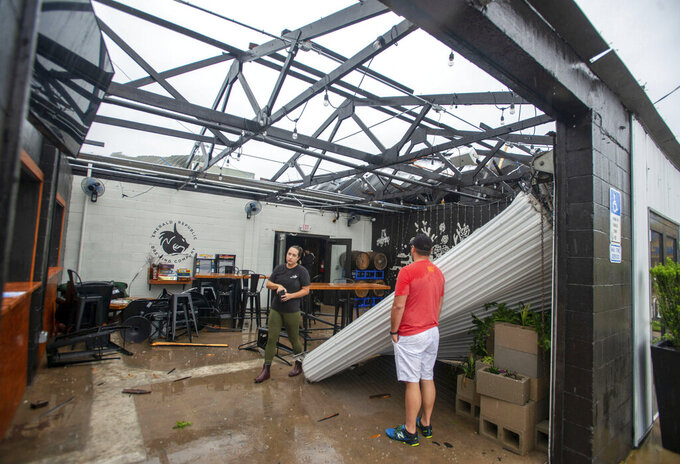 Employees assess the damage after the storm that came through Pensacola, Fla., and blew the roof off of Emerald Republic Brewing on Saturday, April 10, 2021. (John Blackie/Pensacola News Journal via AP)