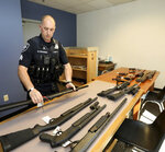In this May 23, 2018, photo, Seattle Police Crisis Response Team Sgt. Eric Pisconski displays guns seized from people deemed to be a danger to themselves or others. Since last year's mass shooting at a Florida high school, states have seen a surge of interest in laws intended to make it easier to disarm people who show signs of being violent or suicidal. Washington voters approved such a law overwhelmingly in 2016. (Greg Gilbert/The Seattle Times via AP)