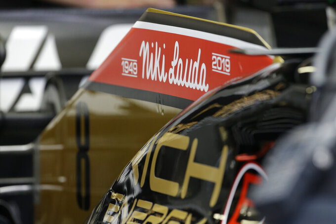 The name of three-time Formula One world champion Niki Lauda is written on Romain Grosjean's Haas race car, top, during the second practice session at the Monaco racetrack, in Monaco, Thursday, May 23, 2019. Three-time Formula One world champion Niki Lauda, who won two of his titles after a horrific crash that left him with serious burns and went on to become a prominent figure in the aviation industry, has died on May 21, 2109. He was 70. (AP Photo/Luca Bruno)