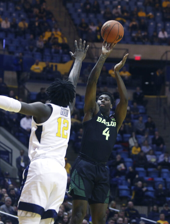 Baylor guard Mario Kegler (4) shoots while defended by West Virginia forward Andrew Gordon (12) during the first half of an NCAA college basketball game Monday, Jan. 21, 2019, in Morgantown, W.Va. (AP Photo/Raymond Thompson)