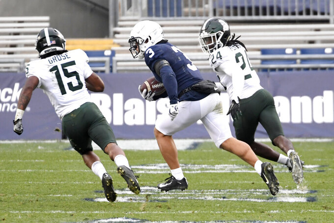 Penn State wide receiver Parker Washington (3) eludes Michigan State defenders Angelo Grose (15) and Tre Person (24) on his way to score a touchdown during the third quarter of an NCAA college football game in State College, Pa., on Saturday, Dec. 12, 2020. Penn State won 39-24. (AP Photo/Barry Reeger)