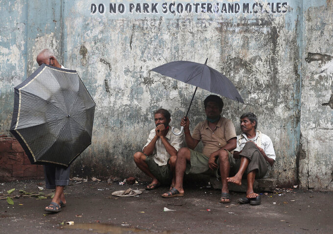 Daily wage laborers wait to be employed for the day, on a street in Mumbai, India, Friday, June 11, 2021. India's economy was on the cusp of recovery from the first pandemic shock when a new wave of infections swept the country, infecting millions, killing hundreds of thousands and forcing many people to stay home. Cases are now tapering off, but prospects for many Indians are drastically worse as salaried jobs vanish, incomes shrink and inequality is rising. (AP Photo/Rafiq Maqbool)