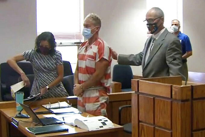"""FILE - In this Thursday, May 6, 2021, file mage from video, Barry Morphew, center, appears in court in Salida, Colo. According to a court document released Monday, Sept. 20 investigators allege that Morphew, charged with killing his missing wife, decided to """"hunt and control"""" her like an animal after she insisted on leaving him and later changed his statements as evidence in the case developed. (KUSA via AP, Pool, File)"""