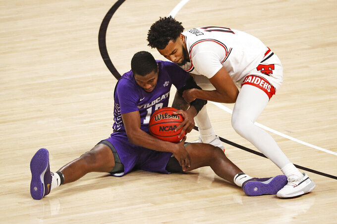 Abilene Christian's Mahki Morris (12) and Texas Tech's Kyler Edwards (11) reach for a loose ball during the first half of an NCAA college basketball game Wednesday, Dec. 9, 2020, in Lubbock, Texas. (AP Photo/Brad Tollefson)