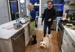 """Sen. Kirsten Gillibrand, D-N.Y., prepares rice for dinner in her kitchen at home in Washington, Tuesday, Feb. 12, 2019, with her husband Jonathan Gillibrand and 2 year-old labradoodle Maple. Gillibrand isn't just embracing her role as a mother on the campaign trail, she's running on it. She opens her stump speech declaring she will """"fight for your children as hard as I would fight for my own.""""(AP Photo/Carolyn Kaster)"""