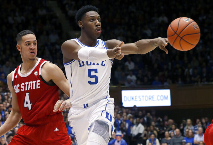 File-This Feb. 16, 2019, file photo shows Duke's RJ Barrett (5) passing the ball against North Carolina State's Jericole Hellems (4) during the second half of an NCAA college basketball game in Durham, N.C. Barrett leads the Atlantic Coast Conference in scoring. He just recorded Duke's first triple-double in 13 years. And as long as his roommate Zion Williamson is still around, he won't have top-billing for the top-ranked Blue Devils. That's just fine with Barrett. (AP Photo/Chris Seward, File)