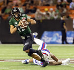 Hawaii quarterback Chevan Cordeiro (12) gets away from Louisiana Tech defensive end Willie Baker, bottom, in the second half of the Hawaii Bowl NCAA college football game, Saturday, Dec. 22, 2018, in Honolulu. (AP Photo/Eugene Tanner)