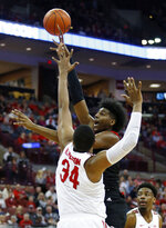 Rutgers forward Myles Johnson, center, goes up for a shot between Ohio State forward Kaleb Wesson, left, and forward Andre Wesson during the first half of an NCAA college basketball game in Columbus, Ohio, Saturday, Feb. 2, 2019. (AP Photo/Paul Vernon)