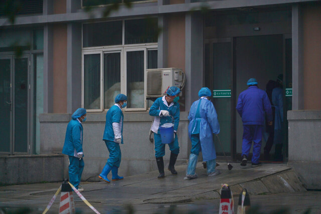 FILE - In this Jan. 22, 2020, file photo Hospital staff wash the emergency entrance of Wuhan Medical Treatment Center, where some infected with a new virus are being treated, in Wuhan, China. (AP Photo/Dake Kang, File)