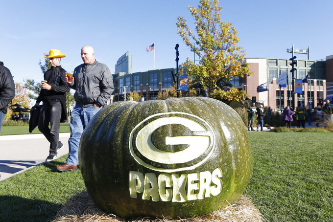 Fans walk outside Lambeau Field before an NFL football game between the Green Bay Packers and the Detroit Lions Monday, Oct. 14, 2019, in Green Bay, Wis. (AP Photo/Jeffrey Phelps)