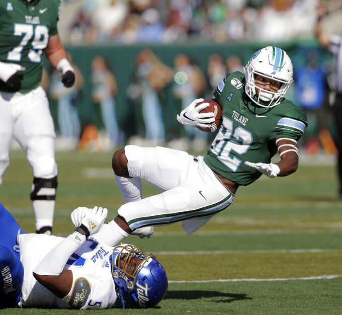 Tulsa defensive tackle Shemarr Robinson (54) tackles Tulane wide receiver Jaetavian Toles (82) during an NCAA college football game in New Orleans, La., Saturday, Nov. 2, 2019. (A.J. Sisco/The Advocate via AP)