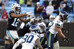 Carolina Panthers wide receiver D.J. Moore (12) reaches for a pass with Seattle Seahawks linebacker Cody Barton (57) and strong safety Bradley McDougald (30) defending during the second half of an NFL football game in Charlotte, N.C., Sunday, Dec. 15, 2019. (AP Photo/Mike McCarn)